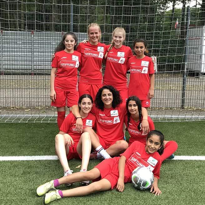 Tuğba mit ihrem Scoring Girls Mädchen in einem Trikotsatz der Köln Stiftung