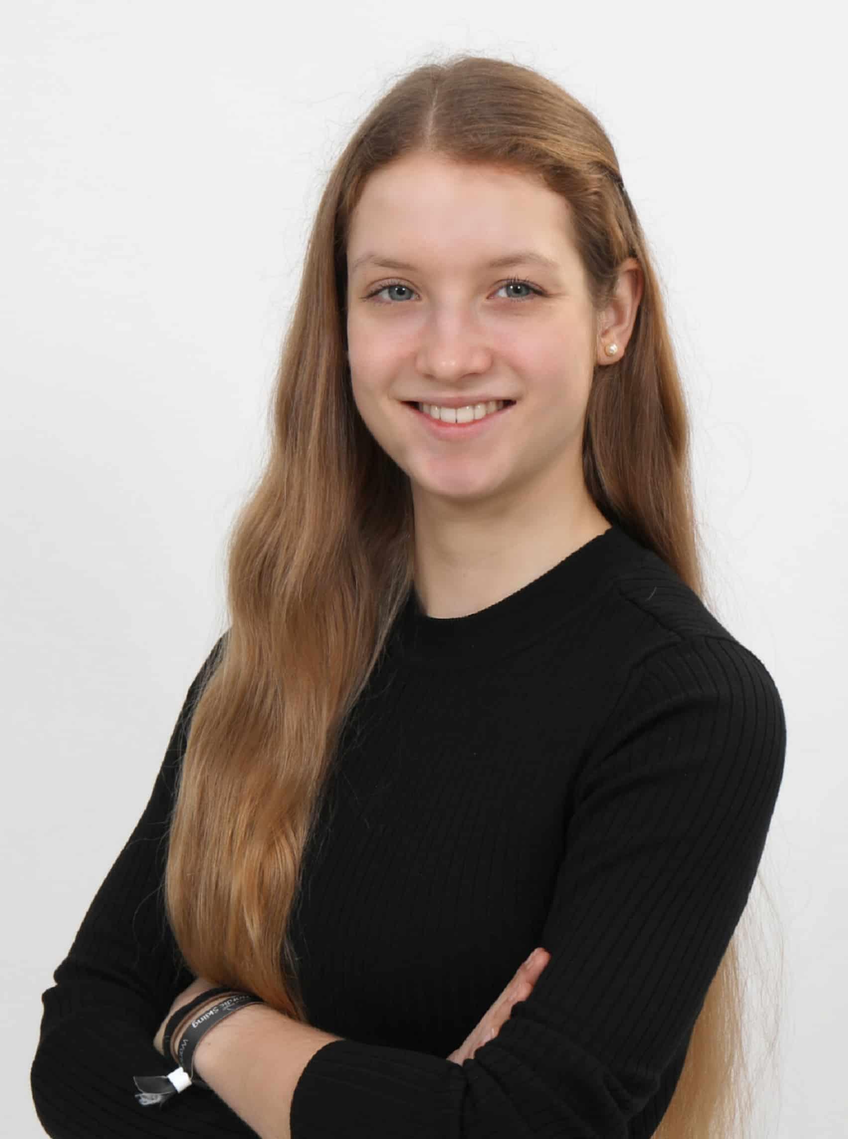 Profilbild Hannah. Sie steht vor einer weißen Wand und hat die Arme verschränkt.