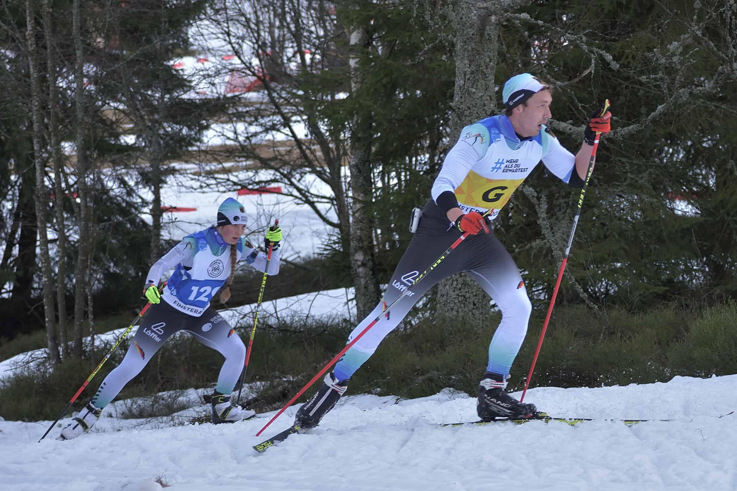 Johanna und ihr Begleitläufer bei einem Wettkampf. Beide kraxeln auf Skiern einen Anstieg im Schnee hoch.