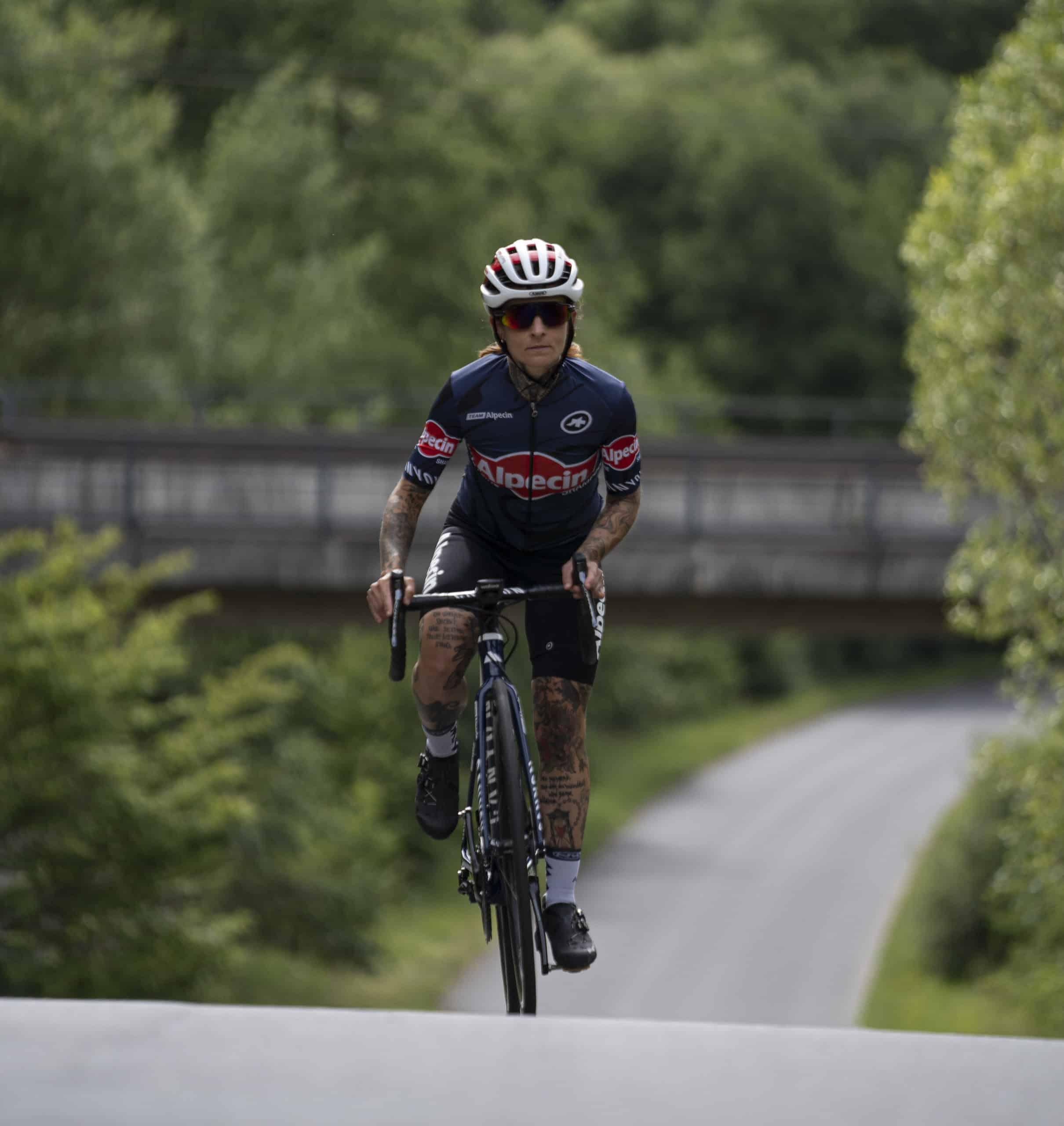 Valeska beim Training auf ihrem Fahrrad auf einer Straße fahrend.