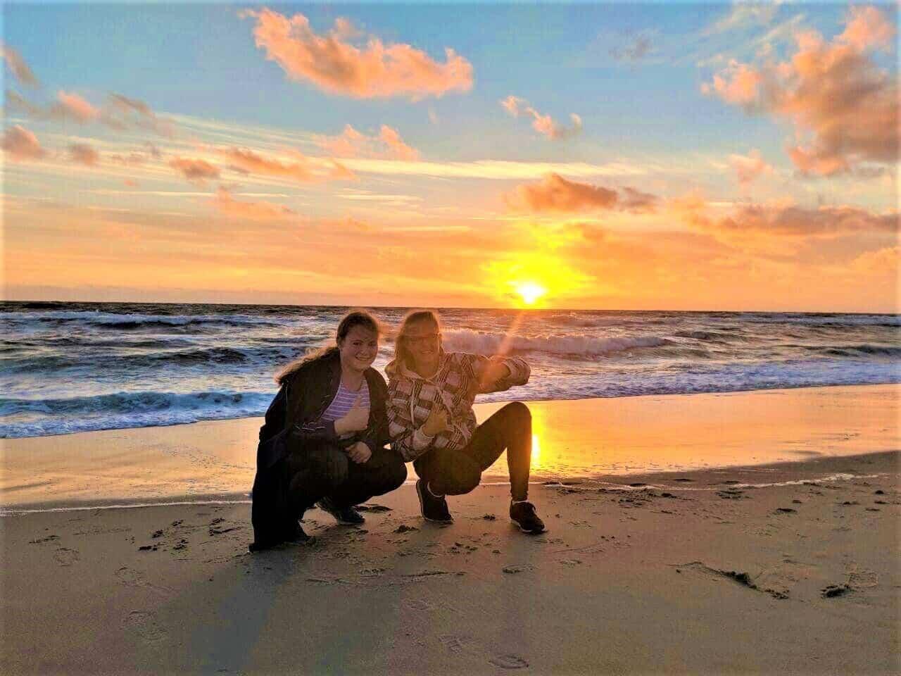 In der Bildmitte sieht man uns (die beiden Lilliys) hockend am Strand nahe des Wassers. Im Hintergrund ist ein Sonnenuntergang. Das Bild ist auf einer Kegeljugendfreizeit auf Sylt entstanden.