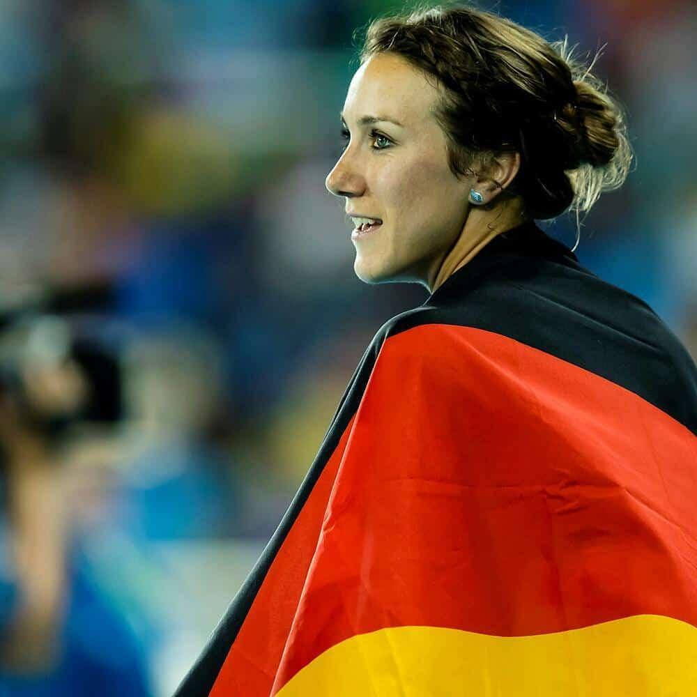 Irmgard bei einem Wettkampf. Ihr hängt eine Deutschlandfahne um die Schultern.