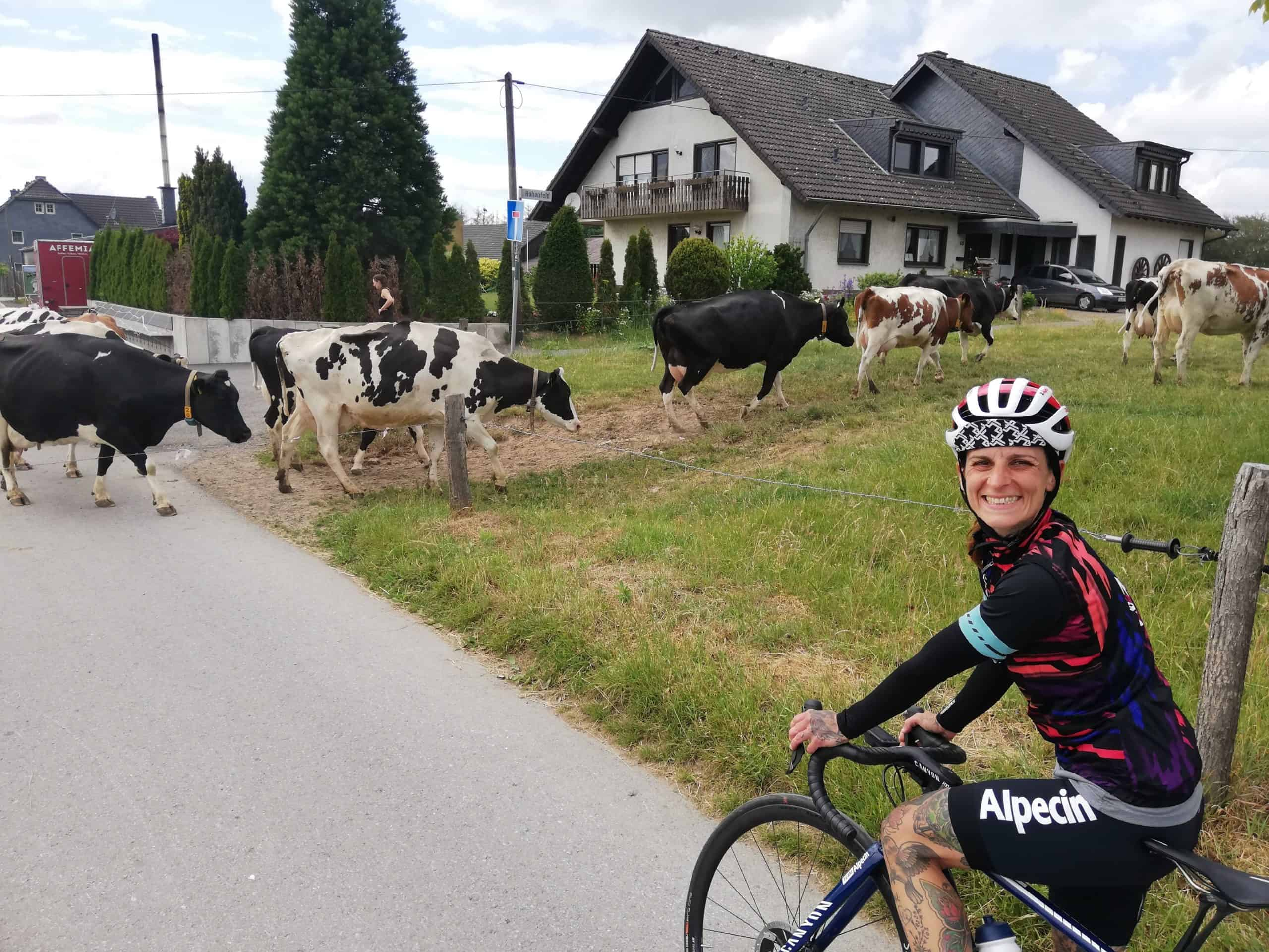 Valeska bei einem Fahrradausflug in einem Dort. Vor ihr stehen Kühe.