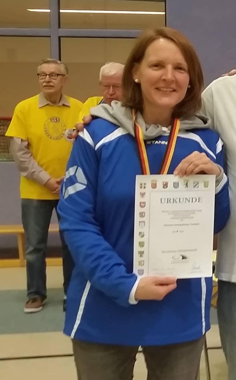 Frauke mit einer Urkunde und Medaille