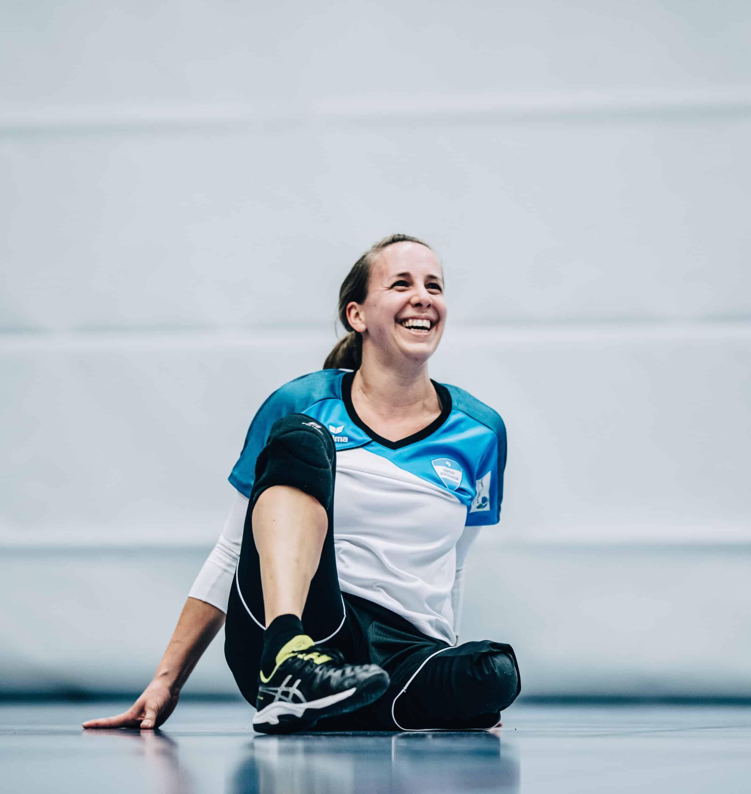 Salome sitzt auf einem Turnhallenboden während eines Volleyballspiels.