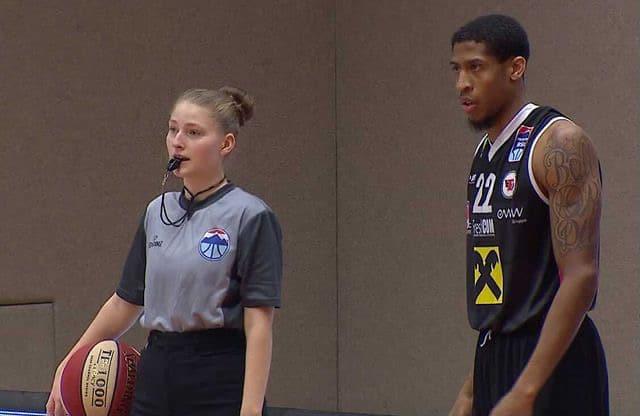 Aurora mit Basketball unterm Arm und Pfeife im Mund. Ein Spieler steht neben ihr.