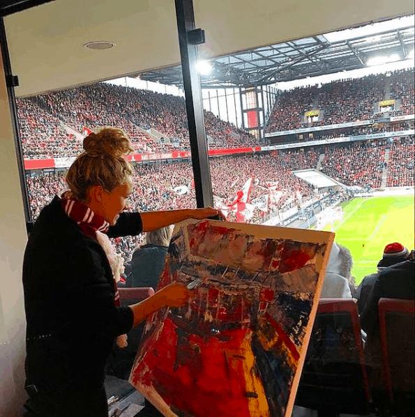 Josephine im Stadion mit einem Kunstwerk in der Hand