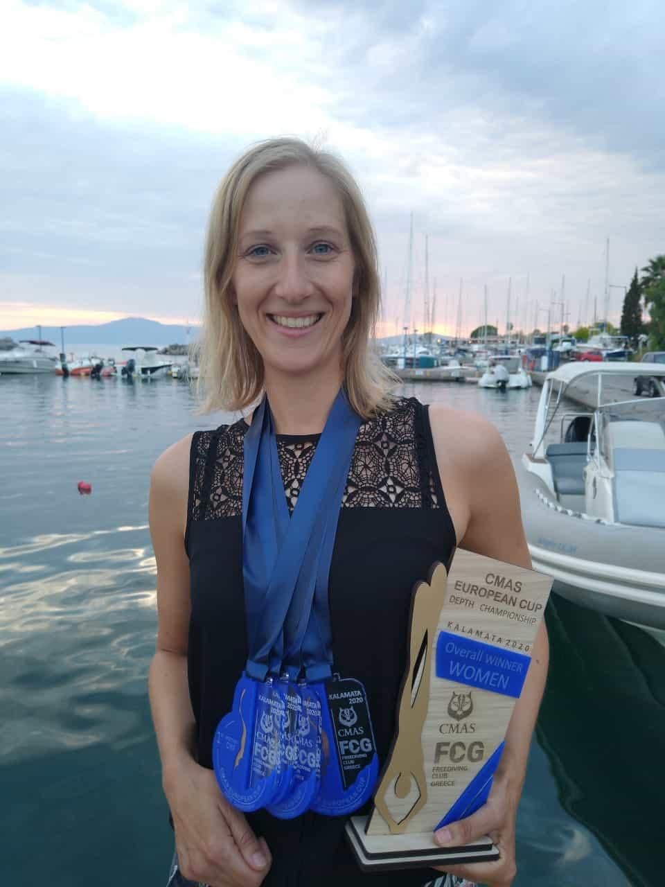 Jennifer vor dem Wasser mit Medaillen und Pokalen